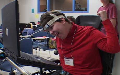 young woman in wheelchair using computer with headstick